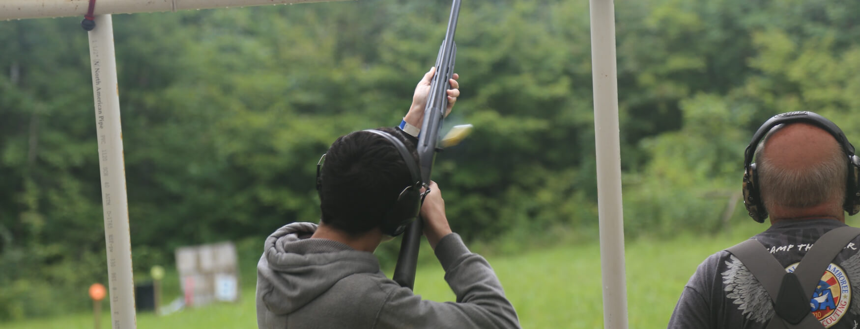 A Scout shoots a shotgun at the camp range